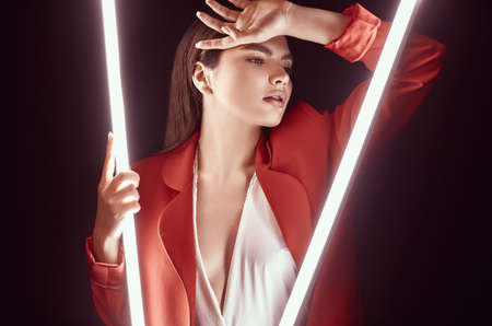 Photo for Portrait of elegant beautiful woman in a red fashionable suit posing around glowing neon lights - Royalty Free Image