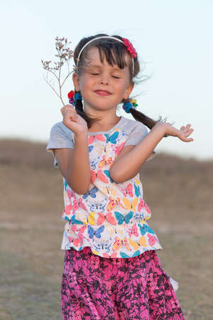 Portrait of little girl with pigtails. Preschooler girl posing with eyes closed outdoors in evening time