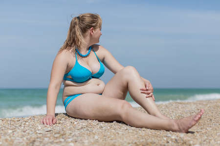 Photo pour Overweight blond at the sea. Adult plump woman in bikini sitting on pebble against the sea - image libre de droit