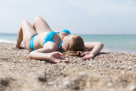 Photo pour Overweight blonde sunbathing on pebble seashore. Adult plump woman in blue bikini lying on back with arms raised - image libre de droit