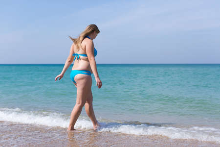 Photo pour Overweight middle aged woman on sand beach. Overweight woman in blue bikini enters the sea water - image libre de droit