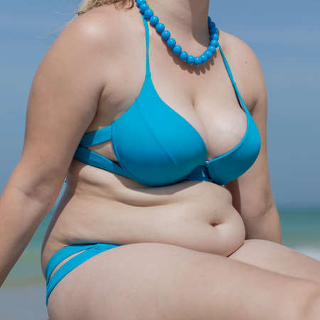 Photo pour Girl on the beach. Torso of adult woman in blue swimsuit and beads, square composition - image libre de droit