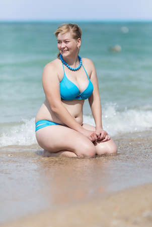Photo pour Overweight blonde at the sea. Adult woman in bikini sitting in waters edge with hands on knees looking away smiling - image libre de droit