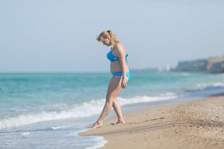 Photo pour Woman in swimwear on sand beach. Overweight woman in swimsuit entering in sea - image libre de droit