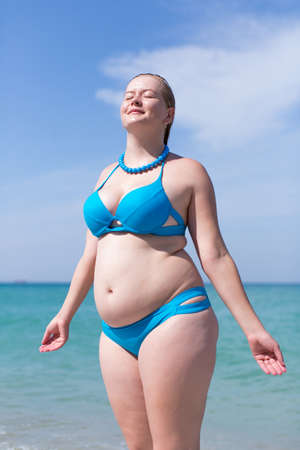 Photo pour Wet overweight middle aged woman at the sea. Wet overweight woman in blue bikini standing with eyes closed and arms outstretched against sea - image libre de droit