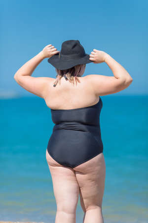 Photo pour Plus-sized woman in black one-piece swimsuit and black hat stands against the sea with arms raised, rear view - image libre de droit