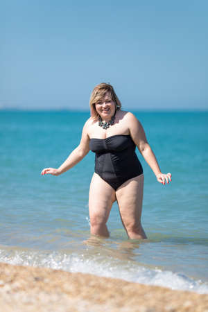 Photo pour Overweight woman in black one-piece swimsuit at the sea. Fat girl comes from sea looking at camera smiling - image libre de droit