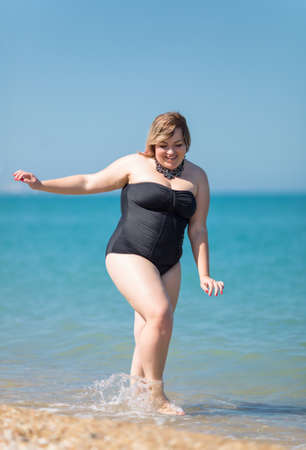 Photo pour Plus-sized woman in black one-piece swimsuit at the sea. Fat girl comes from sea looking down and smiling - image libre de droit