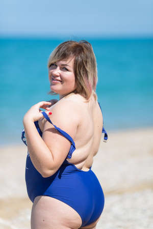 Photo pour Plus-sized woman in blue one-piece swimsuit at the sea. Fat girl in blue swimwear looking at camera over shoulder and smiling - image libre de droit