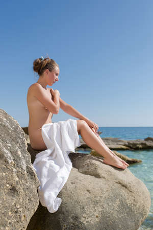 Foto de Girl sunbathing on rocky seashore. Naked young woman with white beach towel on her knees sits on rock and looks at the sea - Imagen libre de derechos