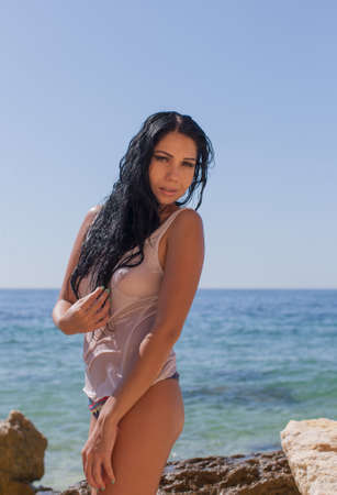 Foto de Dark haired young woman posing in wet tank top at rocky beach. Portrait of attractive sexy brunette woman in wet transparent wear against sea - Imagen libre de derechos