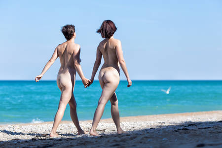 Photo for Homosexual couple at the sea. Two naked female persons walking holding hands along seashore in morning time, rear view - Royalty Free Image