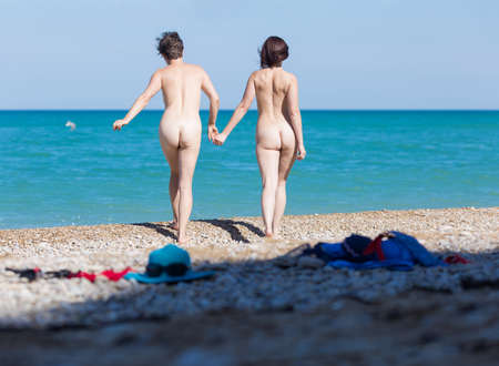 Foto de Homosexual couple on pebble beach. Two naked female persons holding hands going on shingle to the sea, rear view - Imagen libre de derechos