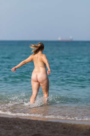 Photo pour Overweight girl on the beach. Naked fat mid adult woman rushes into the sea - image libre de droit