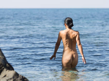 Photo for Skinny-Dipping. Naked dark haired middle aged woman entering in sea - Royalty Free Image