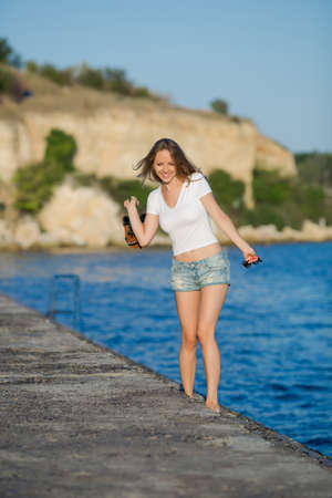 Foto de Barefoot girl in shorts walking on wet concrete quay. Young woman in white T-shirt with sandals and sunglasses in hands going along edge of pier in morning time - Imagen libre de derechos