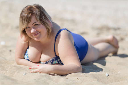 Photo pour Overweight woman in blue one-piece swimsuit at the sea. Fat girl in blue swimwear lying on sand and looking at camera smiling - image libre de droit