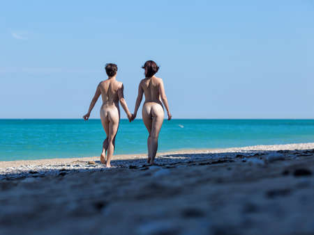 Photo pour Homosexual couple at the sea. Two naked female persons walking holding hands along seashore in morning time, rear view - image libre de droit