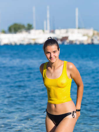 Foto de Dark haired young woman posing in wet tank top at city beach. Portrait of attractive sexy brunette woman in wet transparent wear against sea - Imagen libre de derechos