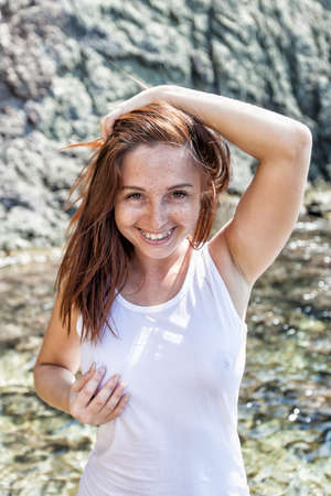 Photo for Portrait of smiling girl in white tank top against rocky seashore. Female person posing with hand on head, she looking at camera laughing - Royalty Free Image