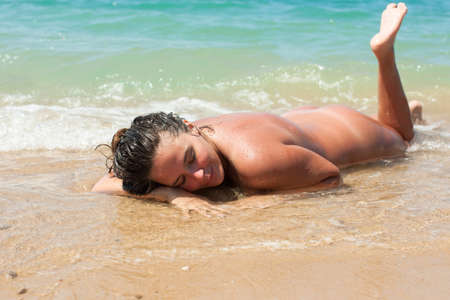 Foto de Female person resting on pebble-sandy beach. Naked young woman lying on front on wet sand in line of surf - Imagen libre de derechos