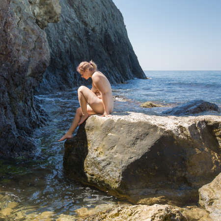 Foto de Young overweight woman resting at the sea. Naked young woman climbs down from stone in sea among coastal rocks - Imagen libre de derechos
