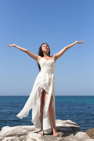 Foto de Girl on rocky beach. Young woman in white dress posing barefoot with arms akimbo and eyes closed on background of coastal rocks - Imagen libre de derechos