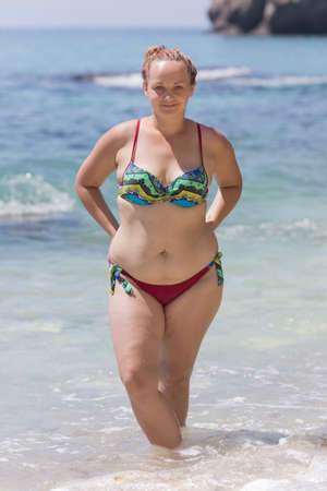 Photo pour Overweight female person resting at the sea. Young chubby woman in bikini posing with arms akimbo. She stands ankle-deep in water and looks at camera smiling a little - image libre de droit