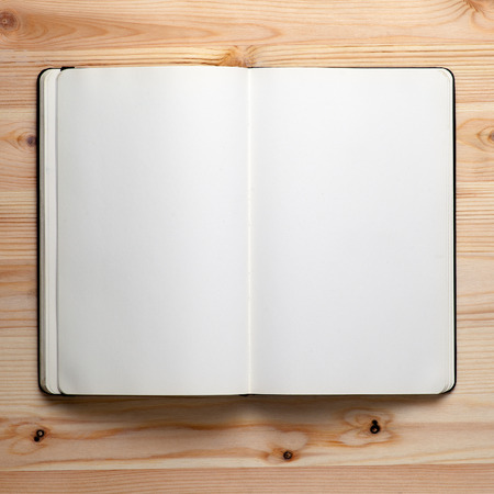 Foto de Open notebook on a wooden table,blank notepad with empty white pages - Imagen libre de derechos