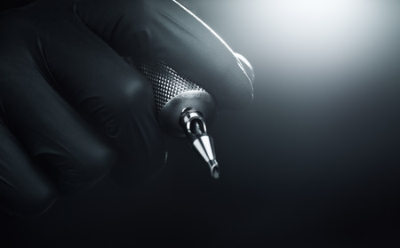 Photo pour Tattooist makes a tattoo Closeup tattoo machine in the hands of selective focus - image libre de droit