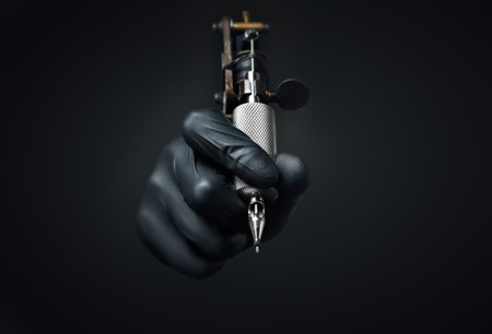 Photo pour Tattoo artist holding tattoo machine on dark background, Machine for a tattoo concept - image libre de droit