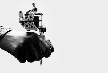 Foto per Tattoo artist holding tattoo machine on light gray background - Immagine Royalty Free