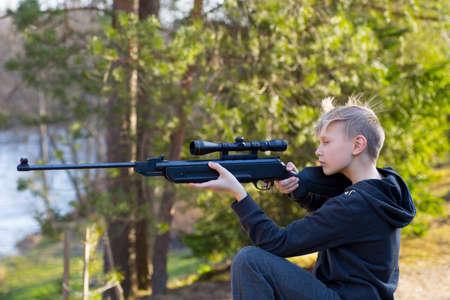 Foto de teenager with air gun in the forest - Imagen libre de derechos
