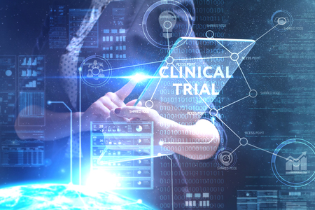 Foto de The concept of business, technology, the Internet and the network. A young entrepreneur working on a virtual screen of the future and sees the inscription: Clinical trial - Imagen libre de derechos