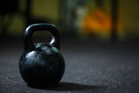Photo for A close-up of steel black kettlebell on a blurred background. A kettlebell on a gym floor. Copy space. - Royalty Free Image