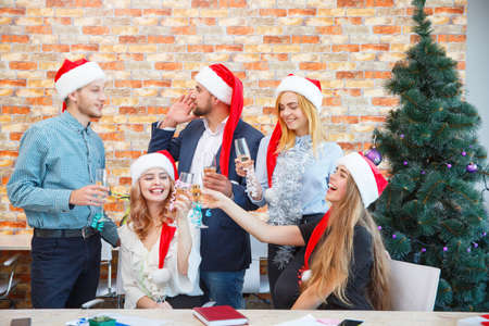 Foto de Happy office team on a Christmas party drinking on a festive background. Christmas cheering concept. - Imagen libre de derechos
