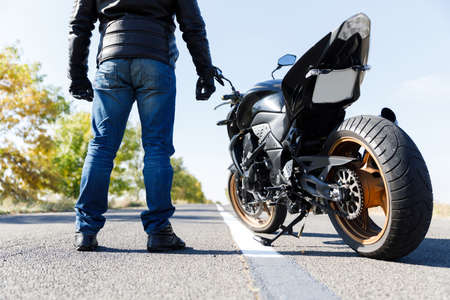 Foto de A close-up of a motorcycle stands on the road with its owner alone - Imagen libre de derechos