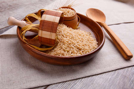Foto de Composition with raw rice in a wooden brown bowl with a wooden spoon and a small bowl. On a gray table covered with a linen tablecloth. - Imagen libre de derechos