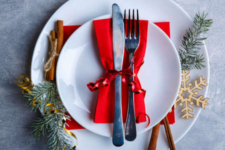 Photo for Plate in a plate with a knife and a fork tied with a ribbon on a red napkin on a stone background. Top view of a closeup - Royalty Free Image