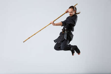 Photo for A ninja man attacks in a jump with a fighting stick on a gray background - Royalty Free Image