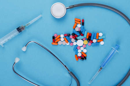 Photo pour On a blue background, there is a layout of medical preparations and instruments, a doctor's stratoscope, a syringe and a bunch of different tablets lined in the form of a cross. View from above. - image libre de droit