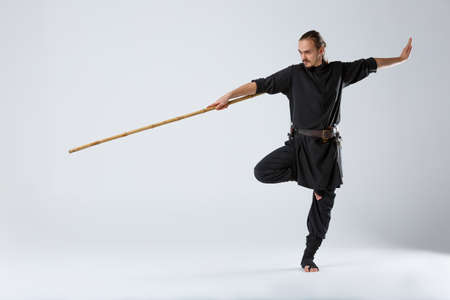 Photo for An experienced fighter, stands in a fighting posture with a fighting bamboo stick. - Royalty Free Image