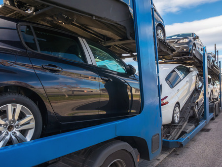 Foto de Some cnew cars in a car transport. Truck car carrier - Imagen libre de derechos