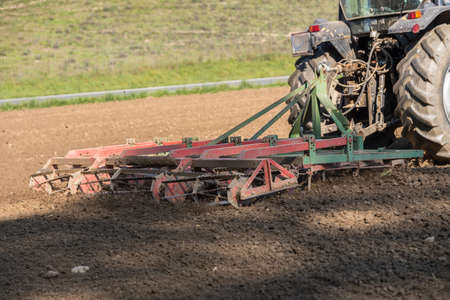 Photo pour Farming a field with tractor and harrow - close-up - image libre de droit