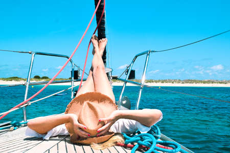 Foto de One female with a hat with her feet at the mast of a sailboat - Imagen libre de derechos