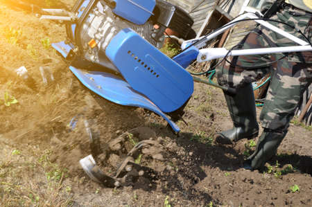Photo pour plowing the land in the garden with a cultivator. agricultural work on plowing the field for sowing seeds. a man plows the land with the help of motor cultivator. - image libre de droit