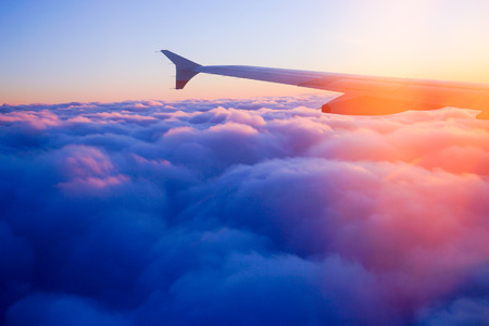 Photo for Airplane Wing in Flight from window, sunset sky - Royalty Free Image