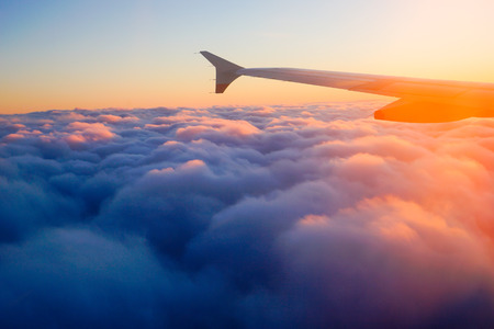 Photo pour Airplane Wing in Flight from window, sunset sky - image libre de droit