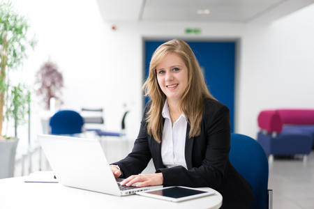Photo for Businesswoman sitting at her desk in an office - Royalty Free Image