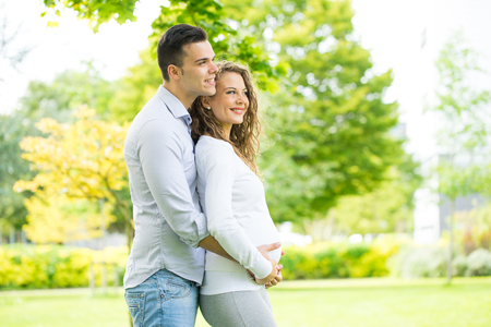 Foto de Happy and young pregnant couple in park in summer - Imagen libre de derechos